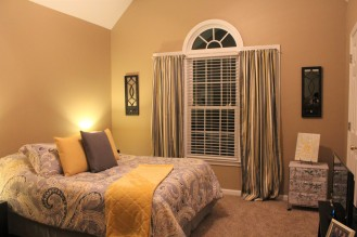 guest bedroom complete with pillows and blanket on bed, window treatments, wall hangings and personal touches
