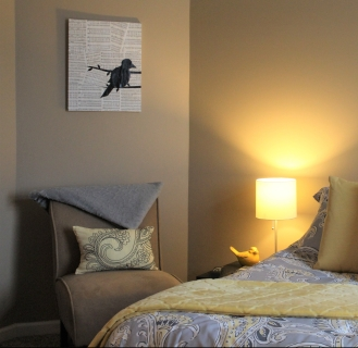 guest bedroom with queen bed and side chair