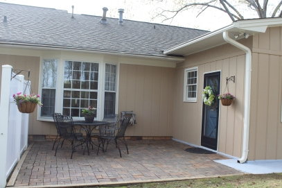 After photo of back patio, complete with pressured washed flooring, dining set, and flowers