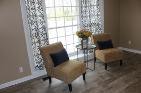 Living room staged with matching window treatments, club chairs and side table
