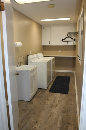 Staged laundry room complete with washer/dryer, sink, storage and hanging space