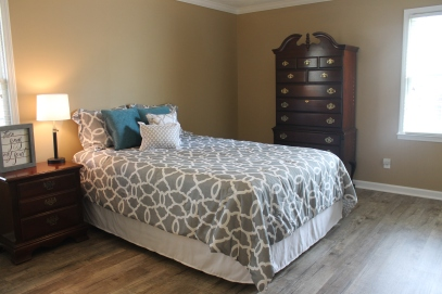 Master bedroom staged with queen bed, side table and wardrobe