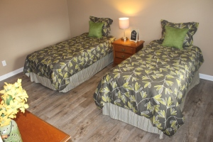 Staged bedroom with twin beds, side table and dresser