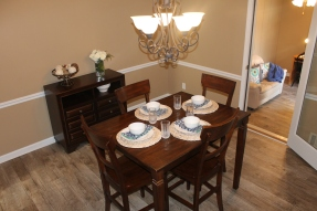Staged dining room complete with light fixture, dressed dining table and buffet